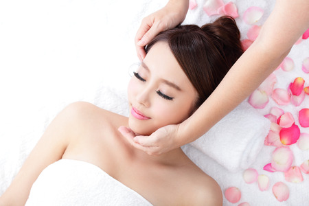 Beautiful young woman enjoy face massage at spa with roses, asian beauty