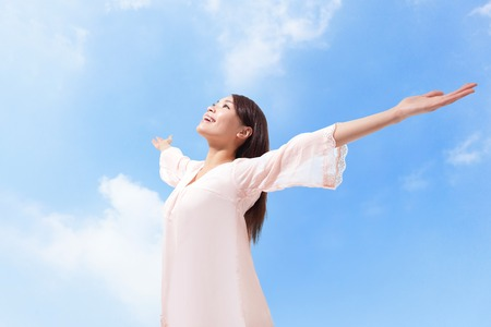 Photo pour Beautiful woman breathing fresh air with raised arms with a cloudy blue sky in the background - image libre de droit