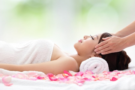 Relax beautiful woman face receiving massage with nature green background, asian beauty