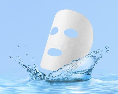 Foto de cloth facial mask with water drop, isolated over blue  - Imagen libre de derechos