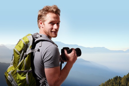 Photo pour Young man with backpack taking a photo on the top of mountains, caucasian - image libre de droit