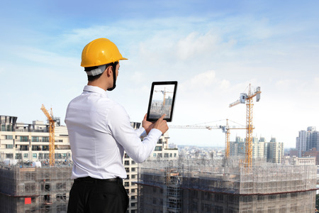Photo pour Rear view of architect looking tablet pc and comparing housing project with building - image libre de droit