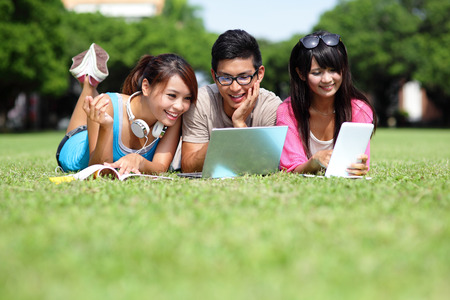Happy College students using laptop and tablet pc on campus lawn, asian