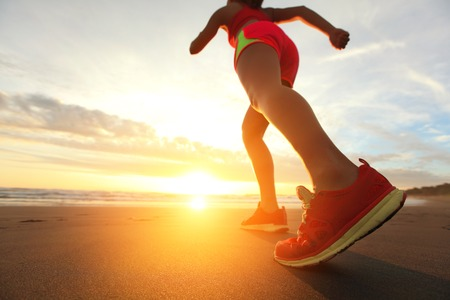 Photo for Woman Runner feet running on the beach at sunrise closeup on shoe. woman fitness sunrise jog workout welness concept. asian - Royalty Free Image