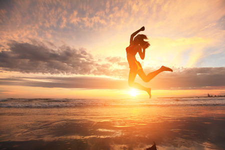 Photo for Happy jump sport young woman running on the beach at sunrise, asian - Royalty Free Image