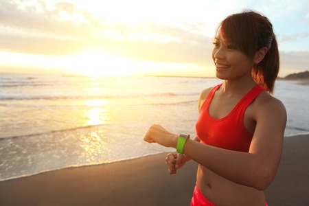Foto per Health sport young woman run and look wear smart watch device with touchscreen on the beach at sunrise, asian - Immagine Royalty Free
