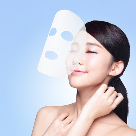 Foto de Relax Young woman with cloth facial mask isolated on blue background, concept for skin care and moisture, asian beauty - Imagen libre de derechos