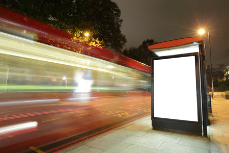 Foto de Blank billboard in bus stop at night with the lights of the cars passing by, great copy space for your design, shot in London, United Kingdom, uk - Imagen libre de derechos