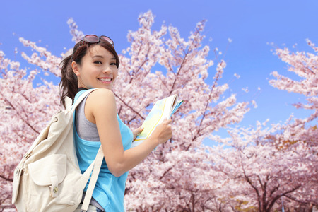 Photo pour Happy travel woman look map and smile with sakura cherry blossoms tree on vacation while spring, asian - image libre de droit