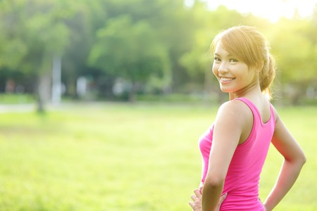 Photo pour Young sport woman stretching and preparing to run in park. asian - image libre de droit