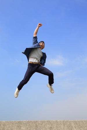 Foto de Happy College student man run and jump with blue sky background, full length, asian male - Imagen libre de derechos