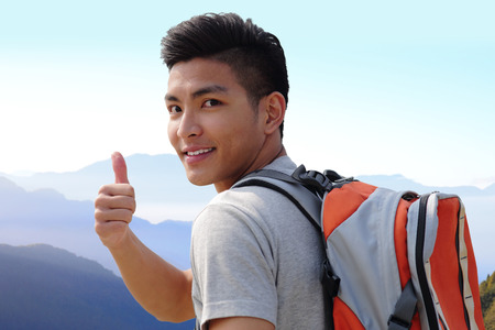 Foto de Successful man mountain hiker with backpack on the top of mountains. asian - Imagen libre de derechos