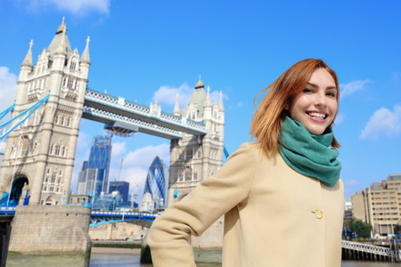 Foto de Happy woman travel in London with tower bridge, and smile to you, caucasian beauty - Imagen libre de derechos