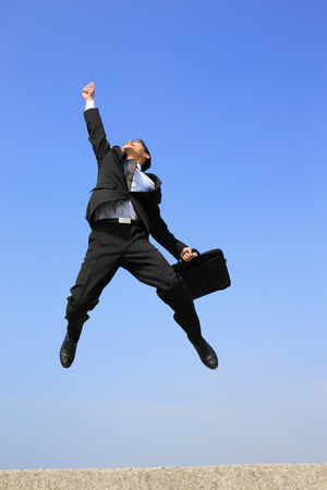 Foto de successful business man jump and run with blue sky background - Imagen libre de derechos