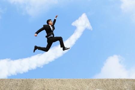 Foto de happy successful business man jump and run with arrow cloud and blue sky background - Imagen libre de derechos