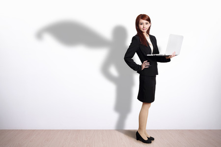 Superhero shadow on Business Woman using laptop computer with white wall background