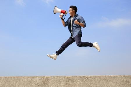 Foto de man jump and shout by megaphone with blue sky background, asian - Imagen libre de derechos