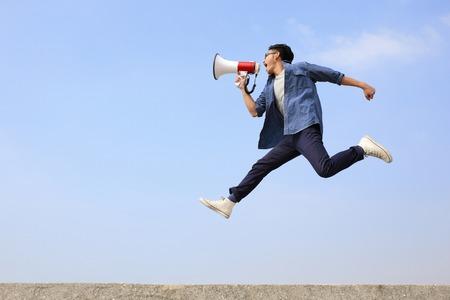 Foto de man jump and shout by megaphone on blue sky background - Imagen libre de derechos