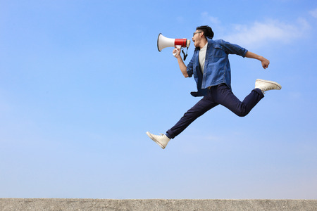 Foto de man jump and shout by megaphone with blue sky background, asian - Imagen libre de derechos