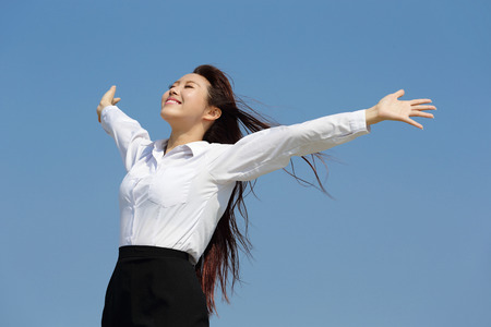 Photo for carefree business woman arms up and feel free isolated on blue sky background, asian beauty - Royalty Free Image
