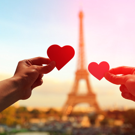 Photo pour silhouette of romantic lovers hand hold love heart paper with eiffel tower in Paris with sunset - image libre de droit