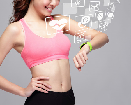 Foto per Health sport woman wearing smart watch device with health icon isolated on gray background, asian beauty - Immagine Royalty Free
