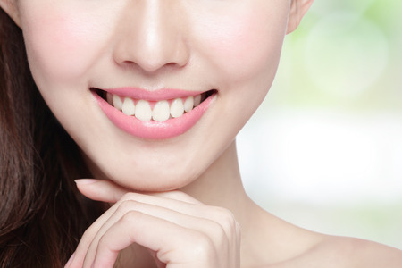 Foto de Beautiful young woman health teeth close up and charming smile. Isolated on green background, asian beauty - Imagen libre de derechos
