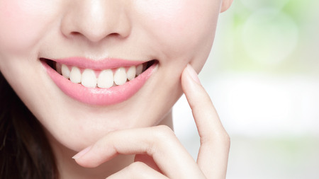 Photo for Beautiful young woman health teeth close up and charming smile. Isolated on green background, asian beauty - Royalty Free Image