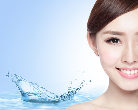 Foto de Beauty Skin care concept, Beautiful woman face with Water splashes isolated on blue background, asian model - Imagen libre de derechos