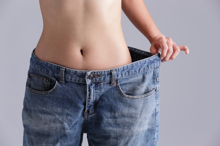 Photo for woman shows weight loss by wearing old jeans, asian beauty - Royalty Free Image