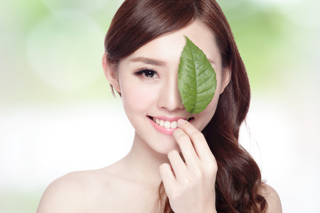 Photo pour beautiful woman face portrait with green leaf , concept for skin care or organic cosmetics , asian beauty - image libre de droit