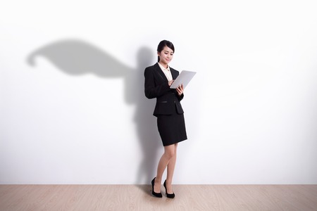 Photo pour Superhero Business Woman using digital tablet pc computer with white wall background, great for your design or text, asian - image libre de droit