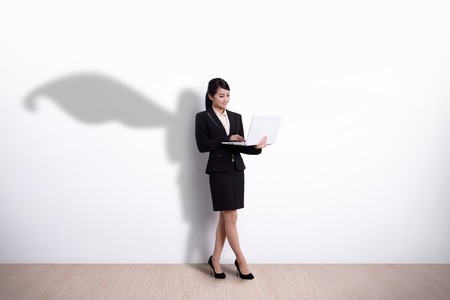 Photo pour Superhero Business Woman using laptop computer with white wall background, great for your design or text, asian - image libre de droit