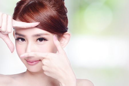 Woman face and eye care and she making frame with hands, asian beauty