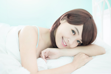 Photo pour Health woman Smile to you and she lying on the bed in the morning , asian girl - image libre de droit