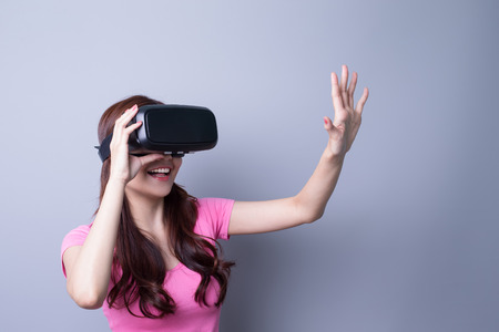 Foto de Smile happy woman getting experience using VR-headset glasses of virtual reality at home much gesticulating hands, asian beauty - Imagen libre de derechos