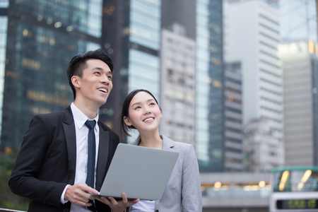 Foto de Business people team meeting with computer in front of the office building, shot in Hong Kong, asian - Imagen libre de derechos