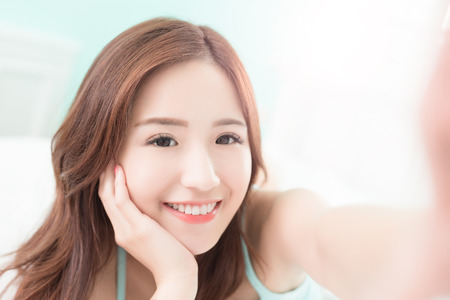 Foto de Health woman Smile take a selfie and she lying on the bed at home , asian girl - Imagen libre de derechos