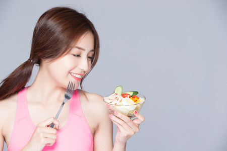 Foto per young woman eat salad and smile isolated gray background - Immagine Royalty Free