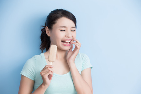 Photo pour woman have sensitive teeth with ice isolatd on blue background, asian - image libre de droit