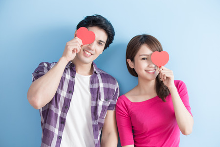 Photo pour Attractive young couple holding red love hearts over eyes isolated on blue background - image libre de droit