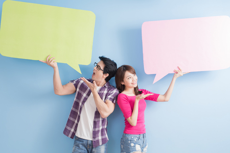 Photo for young couple take speech bubble isolated on blue background - Royalty Free Image