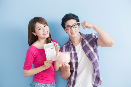 Photo pour young couple hold pink pig bank and calculator isolated on blue background - image libre de droit