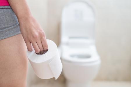Foto de woman take toilet paper in the bathroom - Imagen libre de derechos