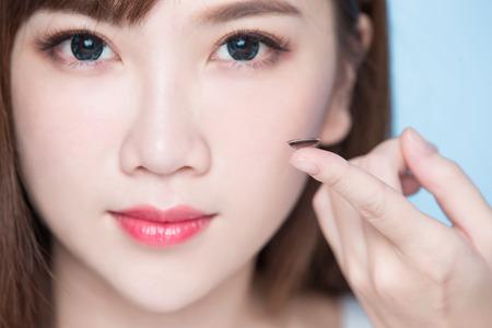 Foto de woman take contact lenses on the blue background - Imagen libre de derechos