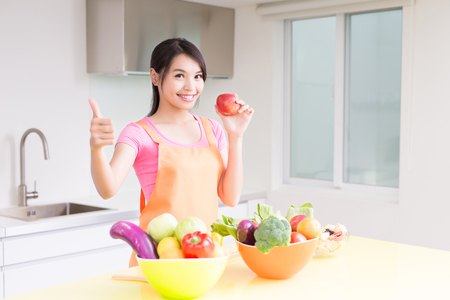 Photo for beauty housewif take apple and thumb up in the kitchen - Royalty Free Image