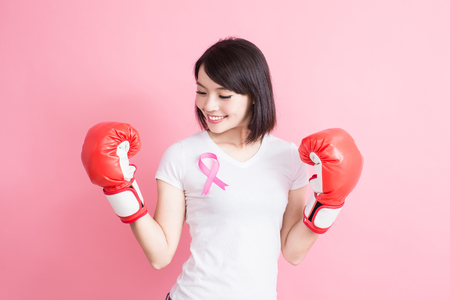 Foto de woman take glove with chest health concept on the pink background - Imagen libre de derechos