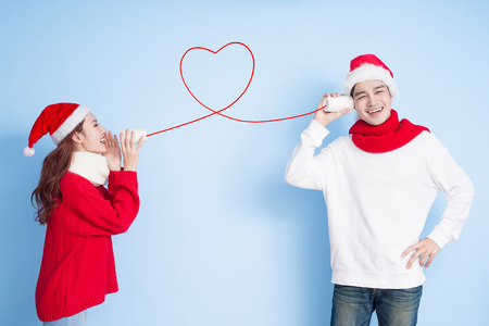 Foto de couple smile and use can phone with merry christmas on the blue background - Imagen libre de derechos