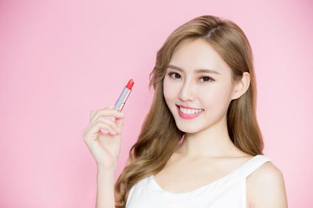 Foto de beauty skincare woman take lipstick on the pink background - Imagen libre de derechos