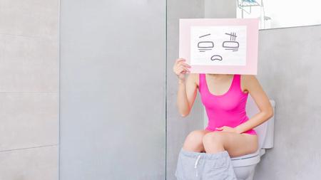 Foto de woman take confuse billboard with constipation in the toilet - Imagen libre de derechos